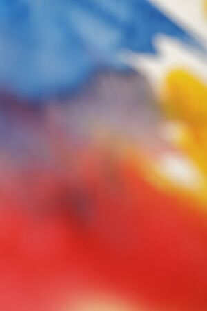 Close up view of blurred yellow, blue and red watercolor paint spills