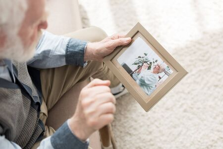Retired man sitting on couch, and holding photo frame in hand