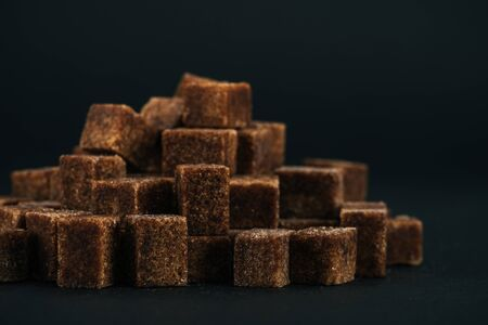 Pile of sweet unrefined brown sugar cubes on black background Stockfoto