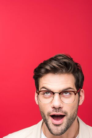 Shocked handsome man in glasses looking up isolated on pink background