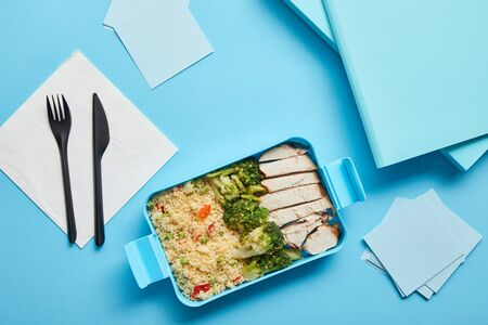 Top view of lunch box with tasty nutritious risotto, chicken and broccoli at workplace on blue background Stock Photo