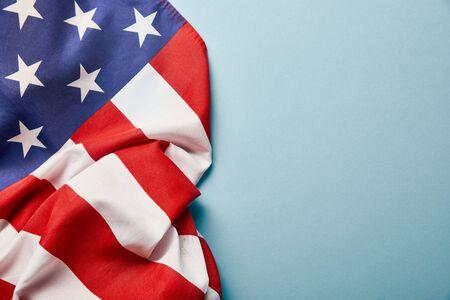 Draufsicht der zerknitterten amerikanischen Flagge auf blauem Hintergrund mit Kopienraum copy Standard-Bild