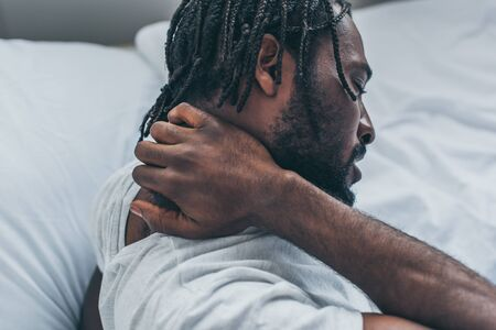 Young African American man with dreadlocks suffering from neck pain in bedroom