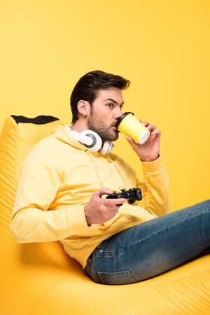 Man drinking coffee to go on bean bag chair and playing video game isolated on yellow background