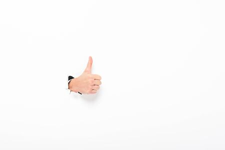 Man showing thumb up from hole in paper wall on white background with copy space