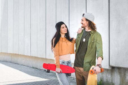 Happy woman in casual wear putting hand on man, standing near concrete wall with skateboard