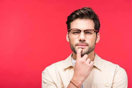 Handsome thoughtful man touching chin isolated on pink background Stock Photo