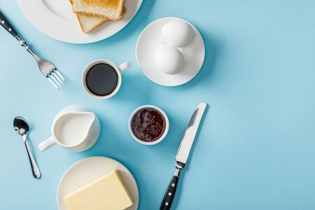 Top view of fresh eggs, jam, coffee, cutlery, butter and two toasts on white plates on blue background