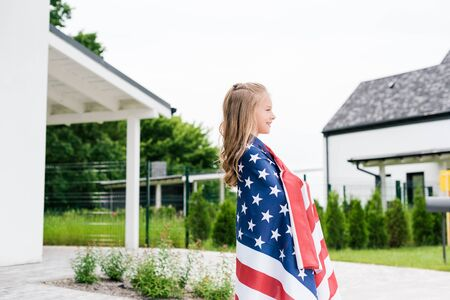 Side view of happy kid smiling while standing with American flag near house