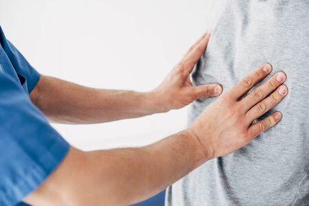 Vista recortada del quiropráctico masajeando la espalda del hombre sobre fondo blanco. Foto de archivo
