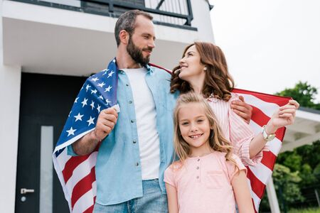 Low angle view of happy kid near cheerful parents with American flag
