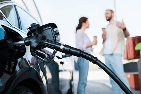 Selective focus of black automobile refueling with benzine near man and woman on gas station