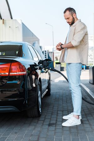 Handsome man standing and looking at watch while refueling black car at gas station Zdjęcie Seryjne