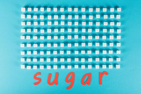 Top view of red paper cut word sugar near rows of sugar cubes on blue surface background
