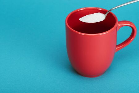 Teaspoonful of white granulated sugar near red cup on blue background