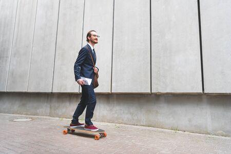 Happy businessman in formal wear riding on skateboard, looking away