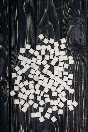 Top view of white sugar cubes on black wooden background