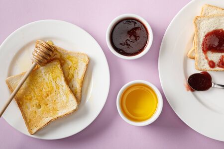 Top view of toasts with jam and honey, bowls and wooden dipper on violet background
