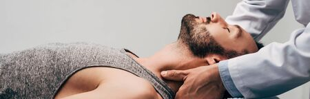 Panoramic shot of chiropractor massaging neck of man on grey background