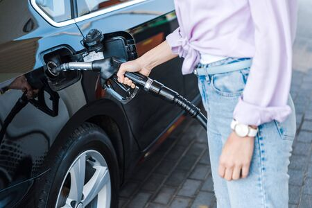 Cropped view of woman holding fuel pump while refueling black car with benzine Zdjęcie Seryjne