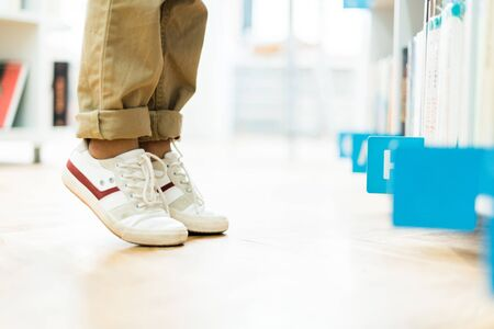 Cropped view of kid standing on tip toe in white sneakers