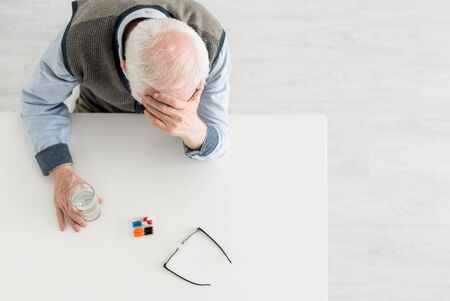 Overhead view of upset elderly man sitting behind table with pills and water in glass