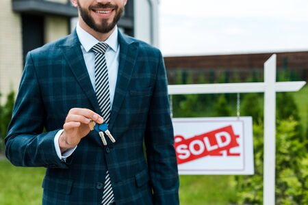 Cropped view of cheerful broker holding keys near board with sold letters Фото со стока