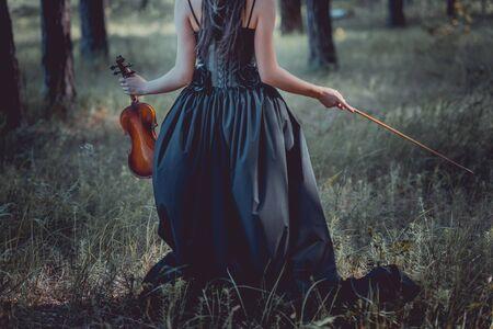 Rückansicht einer Frau im Hexenkostüm, die durch den Wald geht und Geige hält Standard-Bild
