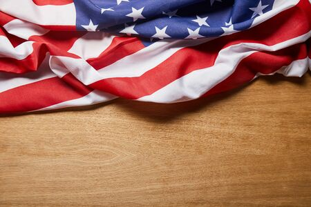 Top view of American flag on beige wooden table with copy space
