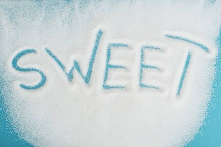 Top view of word sweet made on sprinkled white sugar crystals on blue surface background