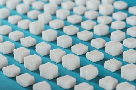 White sugar cubes arranged in rows on blue surface