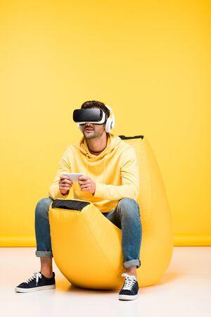 Mann auf Sitzsack mit Smartphone im Virtual-Reality-Headset auf gelbem Hintergrund
