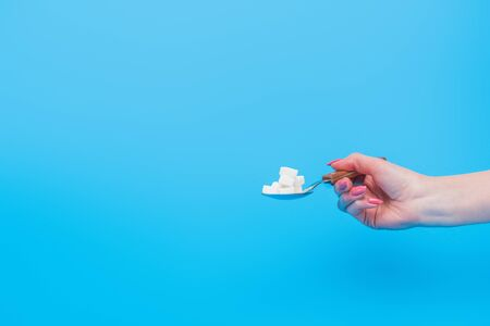 Partial view of female hand with teaspoonful of white sugar cubes isolated on blue background Stock fotó