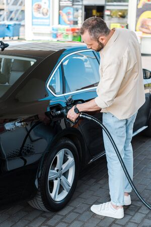 Bearded man refueling black car while standing at gas station
