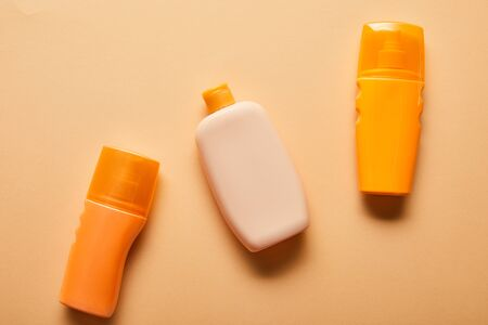 Top view of sunscreen products in bottles on beige background