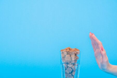 Cropped view of woman showing refuse gesture near glass with brown sugar cubes isolated on blue background Stock Photo