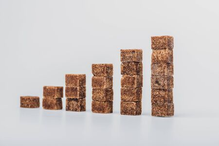 Stack of brown sugar cubes arranged on grey background