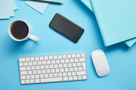 Top view of workplace with cup of coffee, digital devices and papers on blue background Stock Photo