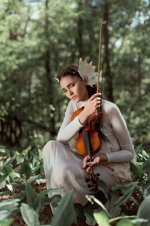Young woman in white swan costume standing on ground with violin, looking at camera