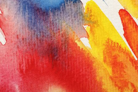 Close up view of wet yellow, blue and red watercolor paint brushstrokes on white background