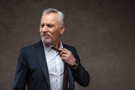 Displeased businessman in suit touching tie on grey background 版權商用圖片