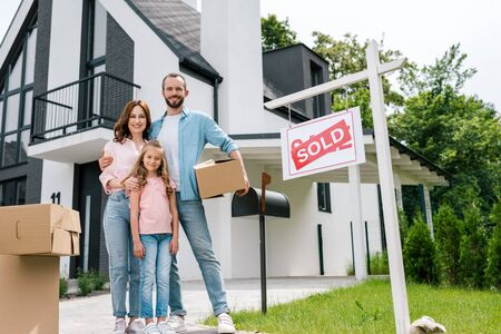 Happy man holding box and standing with wife and daughter near house and board with sold letters