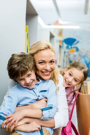Happy woman hugging cute and cheerful boy near smiling kid