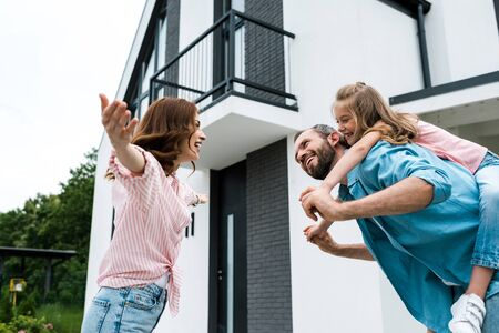 Low angle view of woman with outstretched hands near man piggybacking daughter