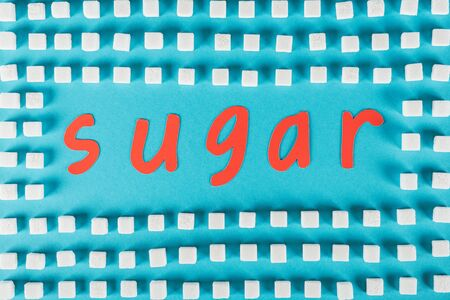 Top view of red paper cut word sugar surrounded by white sugar cubes on blue surface background Imagens - 125529769