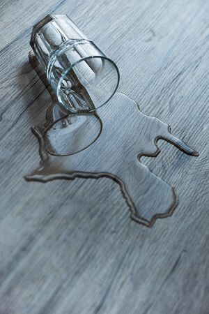 Glass with spilled water on textured wooden surface