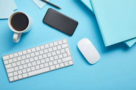 Top view of workspace with digital devices, papers and cup of coffee on blue background