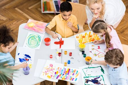 Overhead view of woman looking at multicultural kids painting on papers