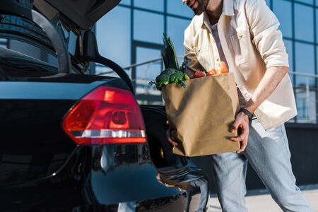 Cropped view of bearded man putting paper bag in car trunk Stockfoto