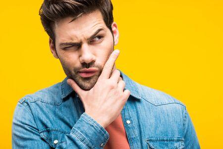 Bel homme confus touchant le menton isolé sur fond jaune